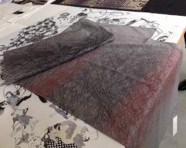 Auf dem Wollschal nimmt ein Gespinst aus Linien Bezug zu einer Szene aus der Erzählung des tschechischen Autors Bohumil Hrabal. Wie das Licht einer Glühbirne kurz vor dem Verlöschen, ändern die Linien ihre Farbe von Grau zu Rosa