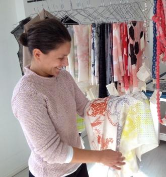 Lenka Kühnertová betrachtet ein mehrfarbig bedrucktes Seidentuch aus der Sonderedition