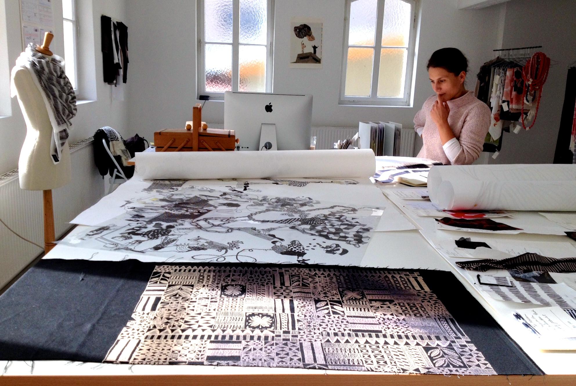 Lenka Kühnertova betrachtet an ihrem Zeichen- und Werktisch ihres Showrooms die Probedrucke ihrer Musterbücher